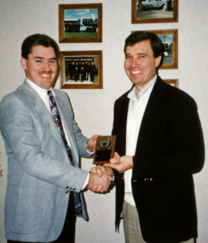"""At the Fort Pierce, Florida, Police Department in 1993, R. Gil Kerlikowske, right, presents an award to R. Sean Baldwin, one of the first police officers that Kerlikowske hired and who now serves as Fort Pierce chief. """"Chief Gil Kerlikowske was an innovative leader who left behind a legacy of community collaboration that still forms the foundation of our policing philosophy,"""" wrote Baldwin for this article. Photo courtesy Fort Pierce Police Department"""