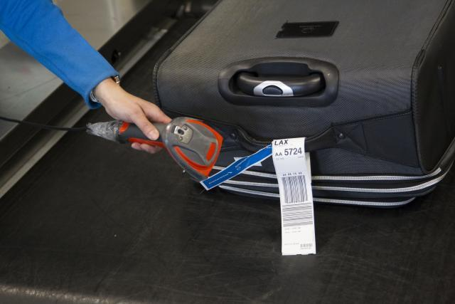Airport personnel scan bar-coded tags on each bag, which is then photographed as it passes into the secure system.
