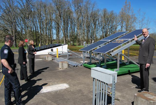 Steve Pecis, SolarWorld's director of operations, demonstrates how solar panels collect the sun's energy on the grounds of SolarWorld's Hillsboro, Oregon facility. CBP Officer William Wells, left foreground; Import Specialist Kristy Huckins, center; and Senior Import Specialist Katie Schultz, far left, listen. Photo by Ed Colford