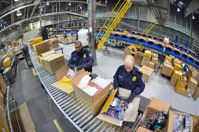 The majority of pirated and counterfeit goods are shipped into the U.S. through international mail and express courier facilities. CBP Officers S. Burns, left, and Cory Bratton inspect shipments of DVDs from China at the Cincinnati DHL facility, one of the busiest express courier hubs.<em> </em>Photos by Brian Bell