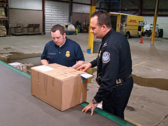 CBP Assistant Area Port Director of Cleveland Eugene Matho, right, and CBP Import Specialist John Parkinson prepare to inspect a shipment of suspected counterfeit DVDs at the DHL Express Courier Distribution Center in Cleveland.<em> </em>Photo by Gary Chaffee
