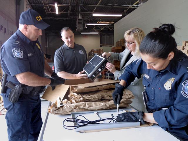 As part of Operation Solar Flare at the port of Charlotte in North Carolina, l-r, CBP Officer Robert Boswell, Import Specialist Jeff Sorrells, Senior Import Specialist Laurie Pazzo, and CBP Officer Joyce Brown examine solar products from China. Photo by Scott Sams