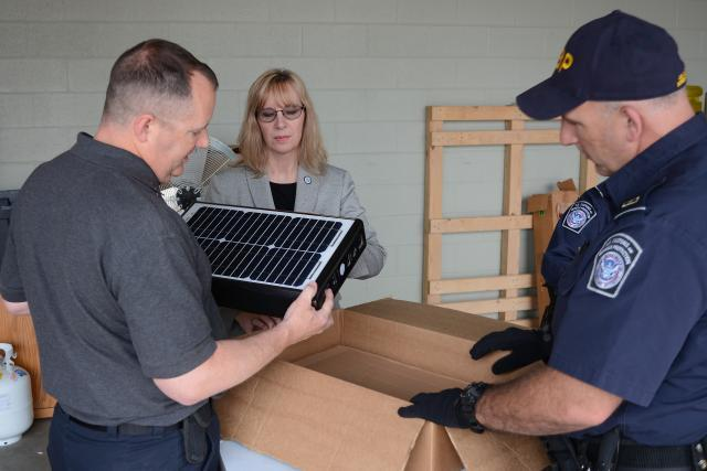 "Import Specialist Jeff Sorrells, left, unpacks a ""solar suitcase"" with CBP Officer Robert Boswell, right, and Senior Import Specialist Laurie Pazzo as part of Operation Solar Flare. Photo by Scott Sams"