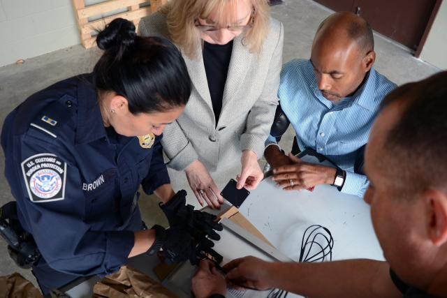 Port of Charlotte team members, l-r, CBP Officer Joyce Brown, Senior Import Specialist Laurie Pazzo, Supervisory Import Specialist Wilbert Jones, and Import Specialist Jeff Sorrells, examine the back of a solar panel to better understand its construction. Photo by Scott Sams