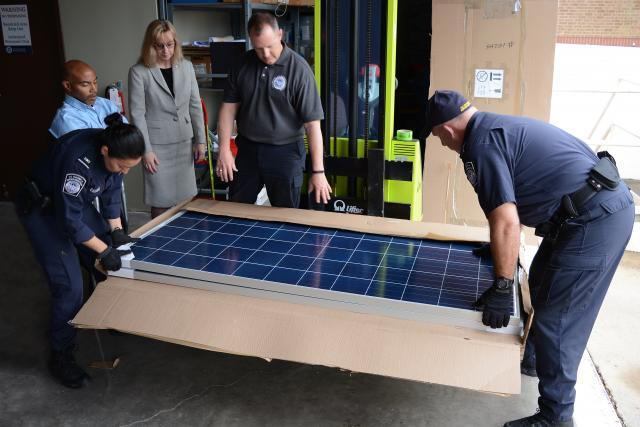 CBP Officers Joyce Brown and Robert Boswell lift a solar panel from its shipping carton as the import specialist team, Wilbert Jones, Laurie Pazzo and Jeff Sorrells, discuss sending a sample to the CBP lab. Photo by Scott Sams