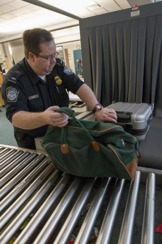 A CBP Vancouver preclearance officer handles bags identified for secondary examination.