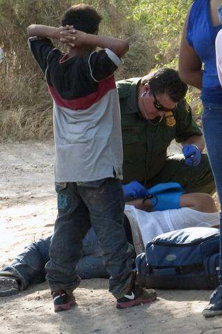 A Border Patrol agent provides treatment and a health assessment of a woman in distress after crossing into U.S. <em>(Photo by Barry Bahler)</em>