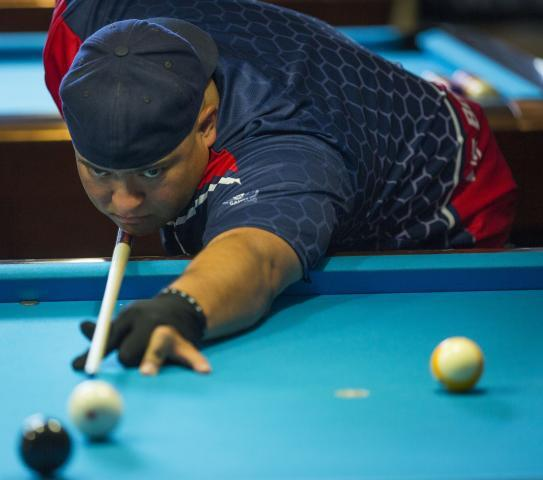 Sighting a winning shot, Border Patrol Agent James Garcia competes in the pocket billiards contest at the 2015 World Police & Fire Games. Photo by James Tourtellotte