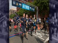 CBP officers and agents carrying flag across the finish line at National Police Week 5k