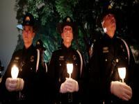 3 CBP officers hold candles at the 2018 National Police Week Candlelight vigil