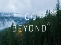 Wooded area with mountains in the background and the text go beyond on top