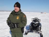 Border Patrol agent standing next to his snowmobile