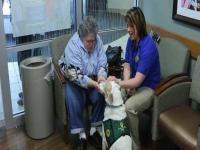 Maya Daniels and her dog Otay provide K-9 therapy to a woman