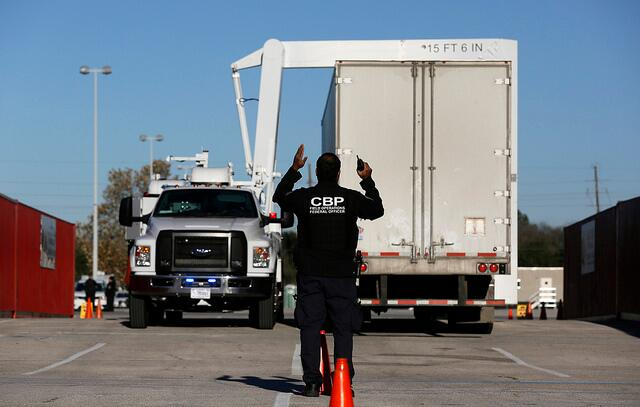A field operations officer guides a CBP x-ray inspection during inspections of commercial vehicles as they arrive at NRG stadium in preparation for Super Bowl LI in Houston, Texas. Photo Credit: Glenn Fawcett