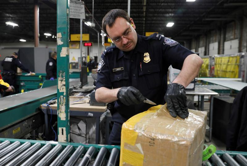 Brian Larson, a CBP officer from Minneapolis, Minnesota, goes through packages at an express carrier consignment facility near the site of this year's Super Bowl.