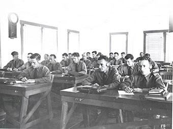34 INS Border Patrol trainees sitting at desks in a classroom