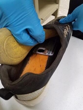 CBP Officer conducts secondary inspection of imposter's shoe and finds read ID card inside
