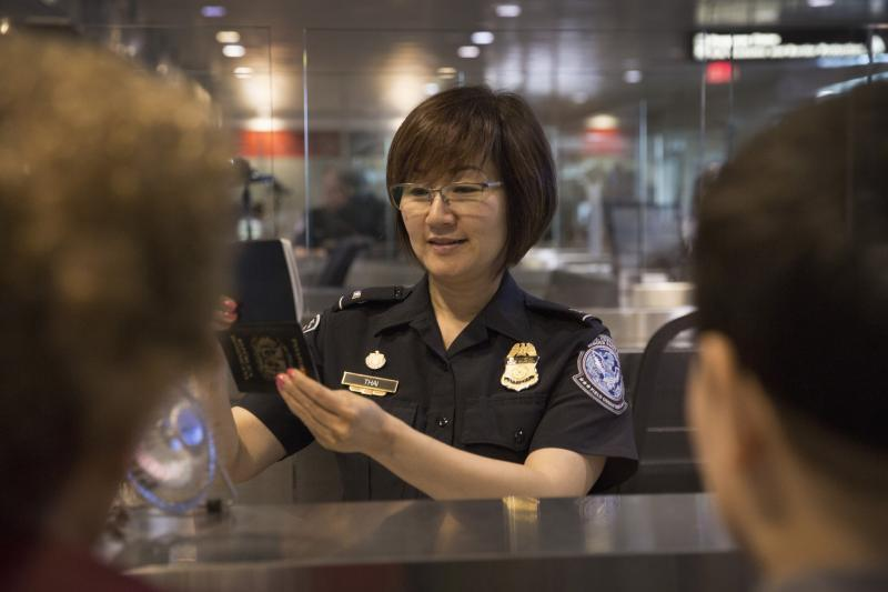 Customs and Border Protection Officer processing travelers