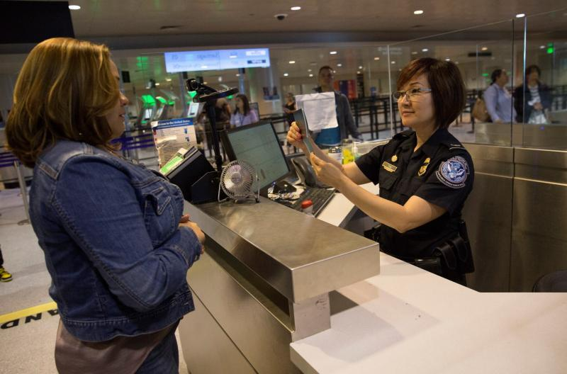 A CBP officer at Boston Logan Airport inspects an arriving traveler.