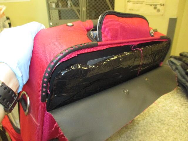 While in a secure area, officers searched the contents of the man's suitcase and discovered two tape-wrapped packages hidden behind an inner lining.