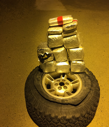 Agents found 12 packages of cocaine and methamphetamine stuffed inside a truck's spare tire.