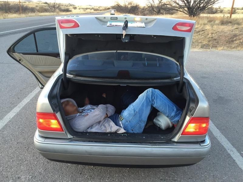 Agents discovered 2 people being smuggled inside the trunk of a car.
