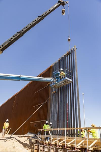 Construction workers install a 30-foot bollard wall panel.