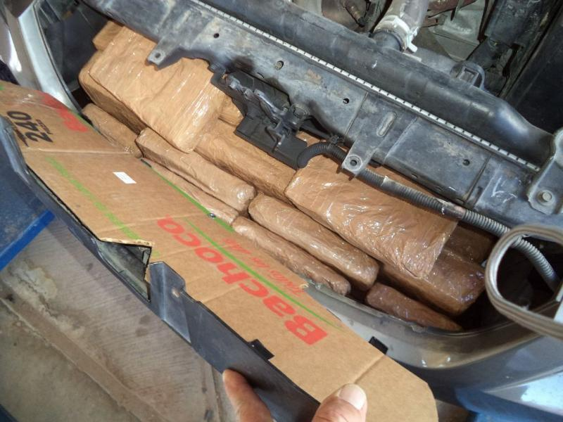 Packages of marijuana underneath hood of a smuggling vehicle