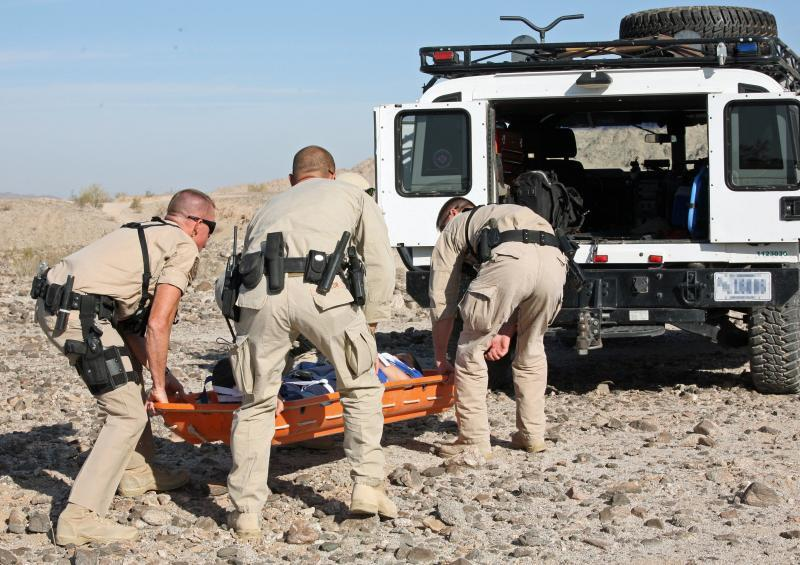 Agents load triaged patient during training scenarios into the back of a BP vehicle
