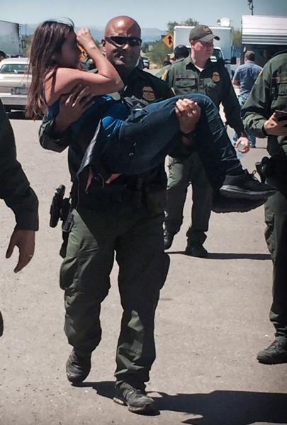 Border Patrol agent carries an injured female who was rescued from the trunk of a smuggling vehicle. The woman was treated by paramedics at the checkpoint.