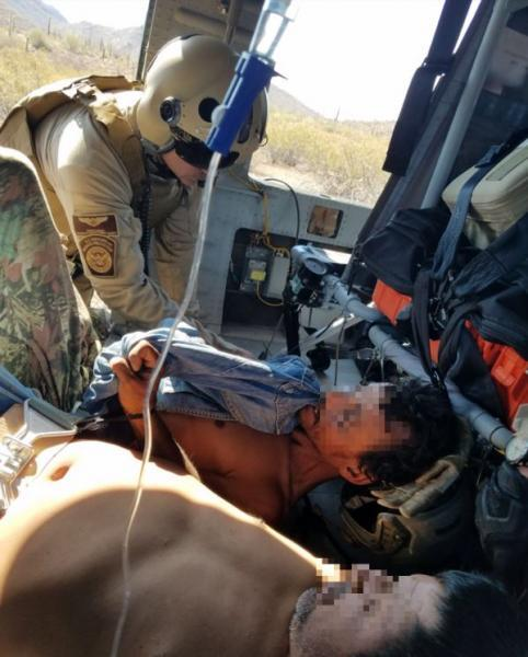 A CBP Air crewmenber triages two illegal aliens who were rescued Tuesday northeast of Ajo