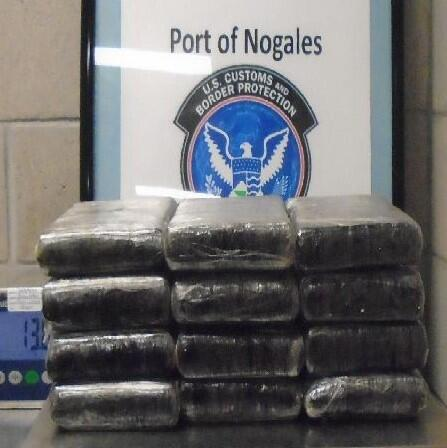Officers removed a dozen packages of cocaine from beneath the seats of a smuggling vehicle