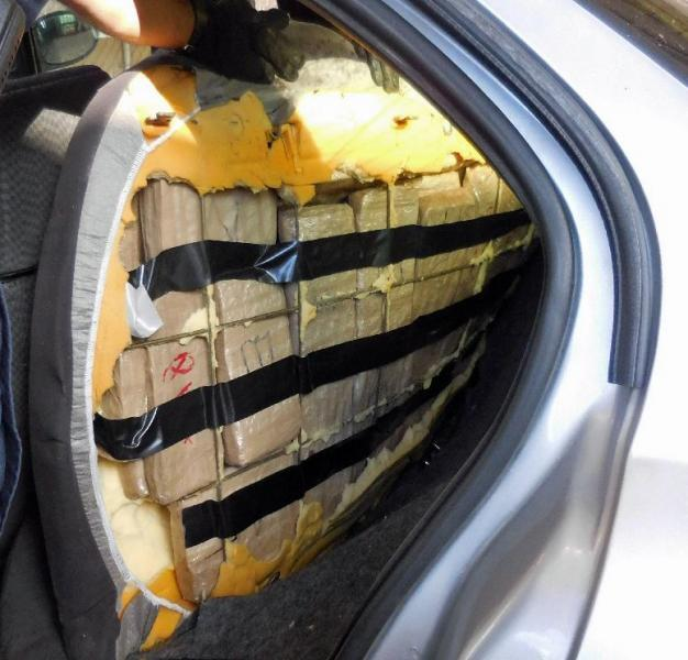 Officers located and seized packages of marijuana from behind the back seats of a smuggling vehicle