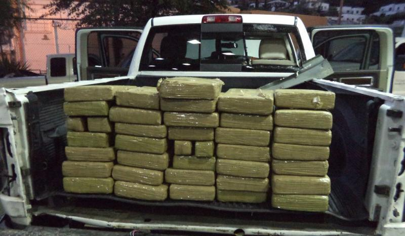 A total of 38 packages of marijuana are removed from a non-factory compartment underneath the truck bed liner of a smuggling vehicle.