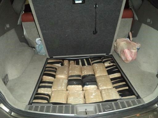 Officers removed packages of marijuana from within the rear compartment of the smugglers vehicle