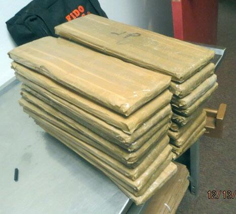 Officers removed and seized 20 packages of marijuana that were hidden beneath the wood slats of a flatbed trailer