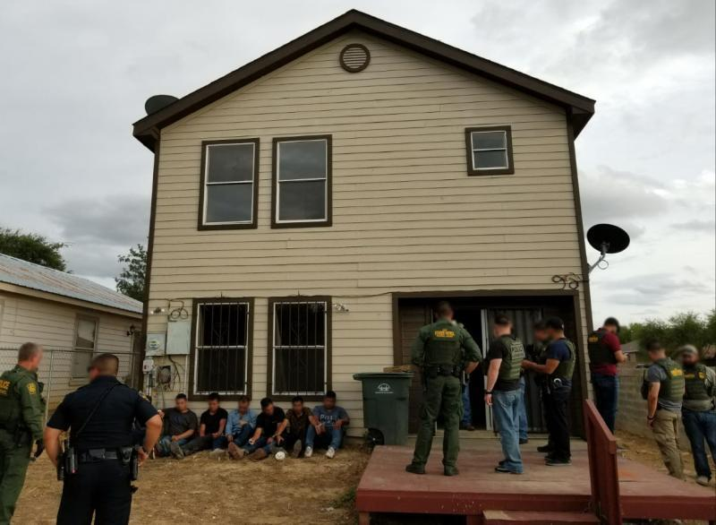 stash house with illegal aliens sitting down in front with BP agents standing in front of them as well as to the side