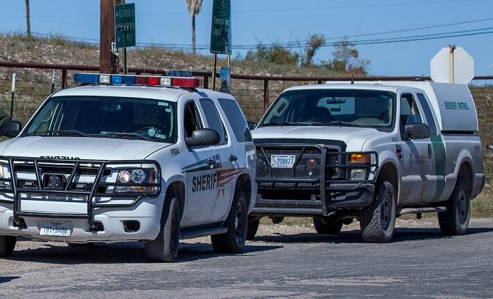 Zavala County Sheriff's vehicle and U.S. Border Patrol vehicle parked along the border