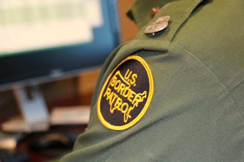 Border Patrol agent performing immigration check on computer