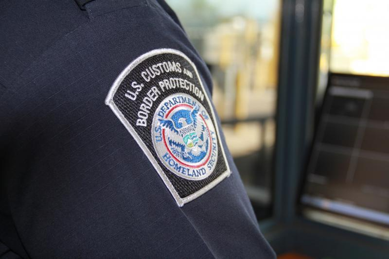 CBP officer sitting at window interviewing a border crosser at the port of entry