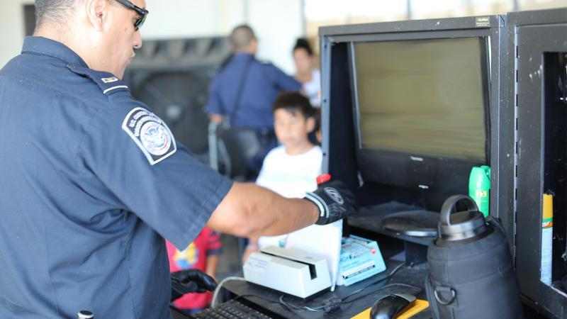 A CBP officer processes arriving bus passengers at Laredo Port of Entry
