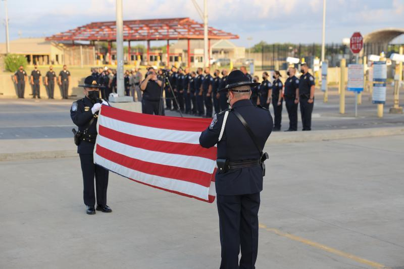 CBP Honor Guard members fold the American flag as a line of officers stands in formation in the background during the 20th anniversary 9/11 memorial ceremony at Veterans International Bridge