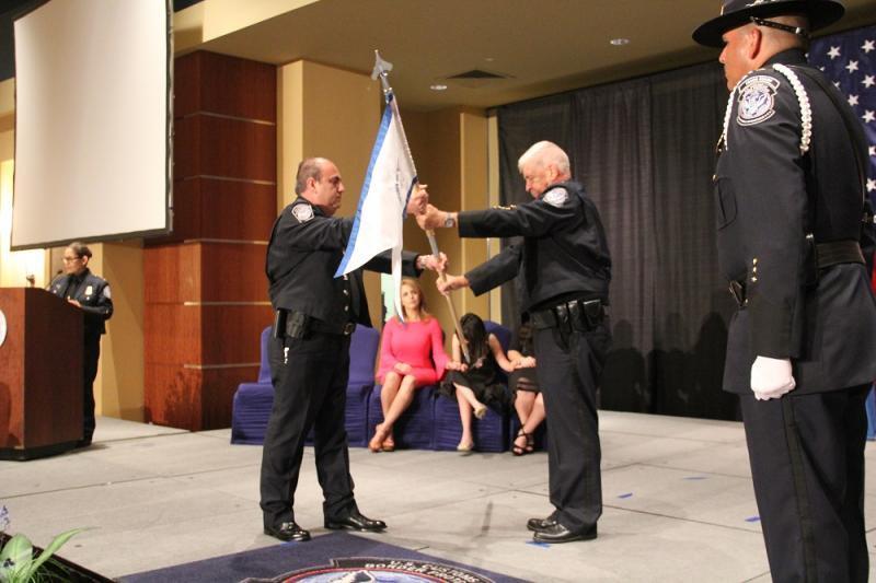 Director del Puerto Carlos Rodriguez recibe la bandera dado por Director, Operaciones Aduaneras David P. Higgerson in una ceremonia de Cambio de Mando.