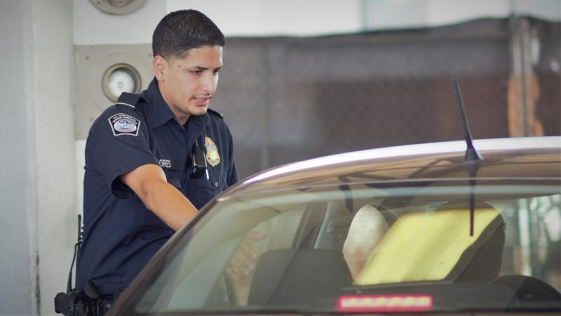 A CBP officer conducts a vehicle priamry examination at Juarez-Lincoln Bridge