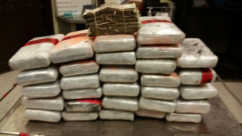 Bundles containing 74 pounds of cocaine and $2,500 in currency seized by CBP officers at Laredo Port of Entry.