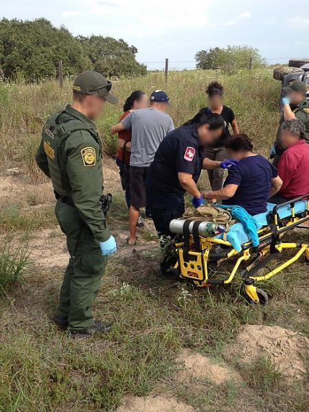 Border Patrol agents and an off-duty OAM pilot assist, comfort victims of a rollover accident as emergency medical personnel arrive on scene to provide medical attention.