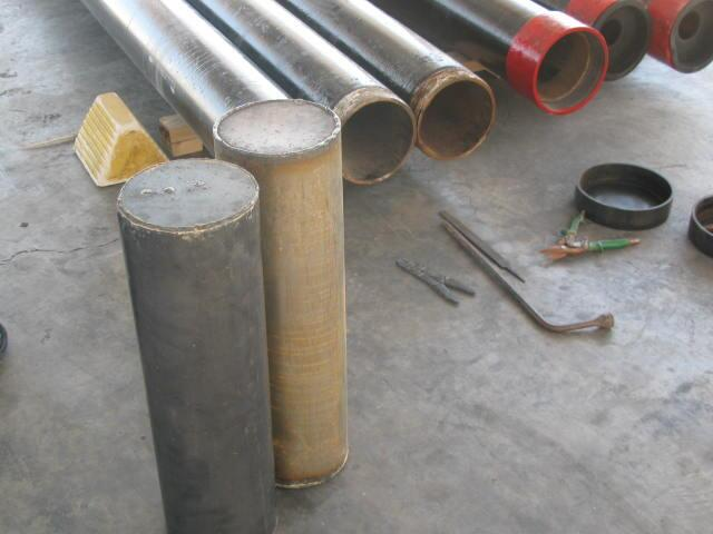 CBP Officers remove marijuana-filled cylinders from metal pipes.