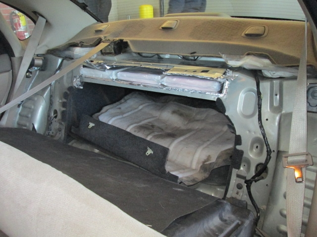 Cocaine bundles visible in hidden compartment.