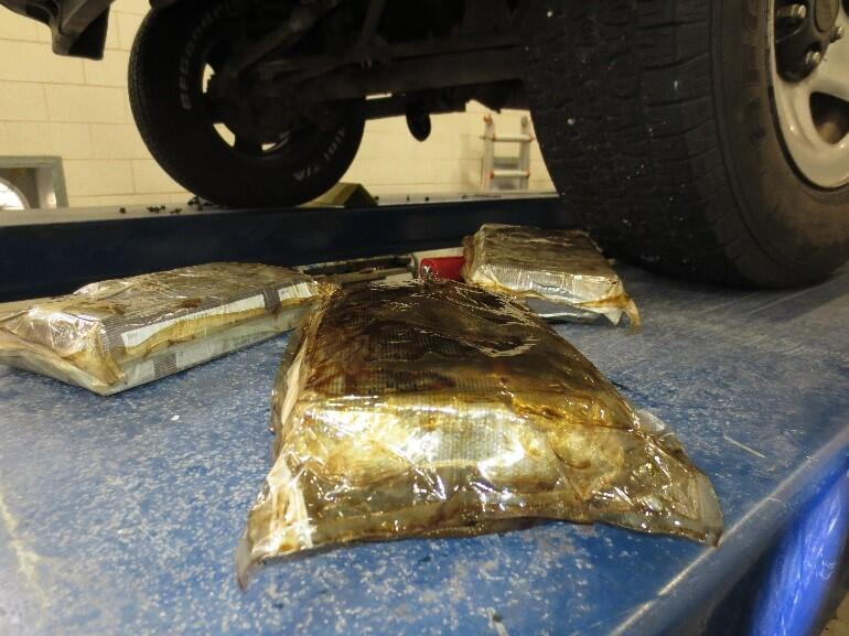 CBP officers remove three bundles of cocaine from oil pan