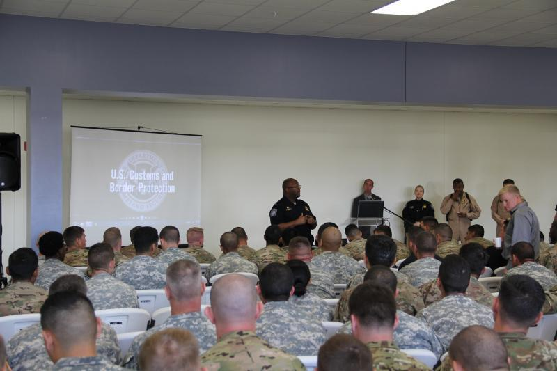 U.S. Customs and Border Protection employees brief Fort Campbell, Kentucky soldiers at a recruitment event.